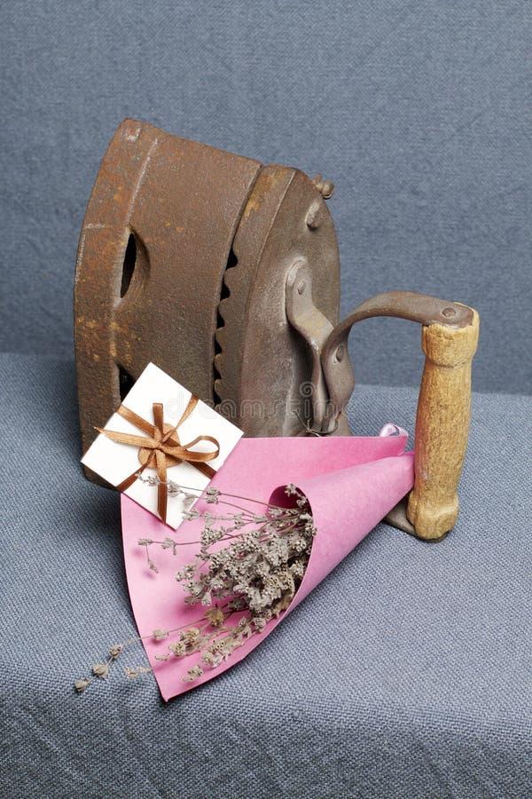 Παλαιός σίδηρος, που θερμαίνεται από τους καυτούς άνθρακες Τοποθετημένος στο γκρίζο ύφασμα Εδώ κοντά είναι ψάθινα καλάθια, μια αν στοκ εικόνα με δικαίωμα ελεύθερης χρήσης