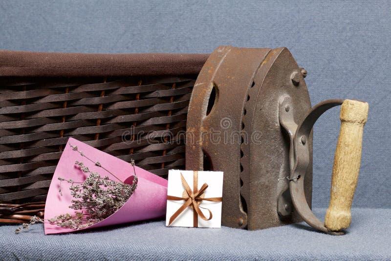 Παλαιός σίδηρος, που θερμαίνεται από τους καυτούς άνθρακες Τοποθετημένος στο γκρίζο ύφασμα Εδώ κοντά είναι ψάθινα καλάθια, μια αν στοκ φωτογραφίες