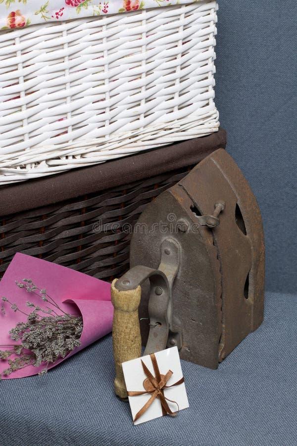 Παλαιός σίδηρος, που θερμαίνεται από τους καυτούς άνθρακες Τοποθετημένος στο γκρίζο ύφασμα Εδώ κοντά είναι ψάθινα καλάθια, μια αν στοκ εικόνα