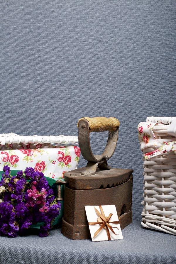 Παλαιός σίδηρος, που θερμαίνεται από τους καυτούς άνθρακες Τοποθετημένος στο γκρίζο ύφασμα Εδώ κοντά είναι ψάθινα καλάθια, μια αν στοκ φωτογραφία