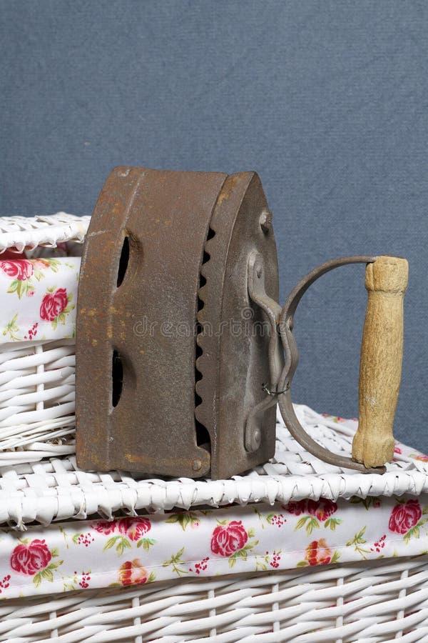 Παλαιός σίδηρος, που θερμαίνεται από τους καυτούς άνθρακες Τοποθετημένος ψάθινα καλάθια στοκ φωτογραφία