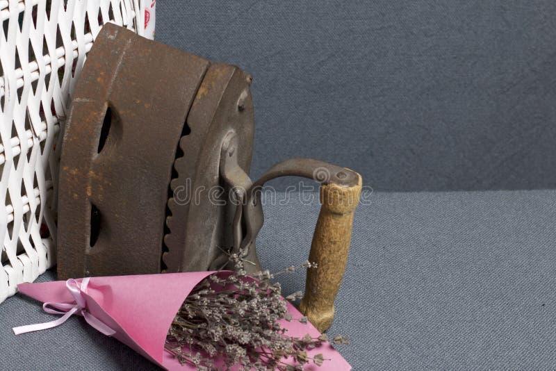 Παλαιός σίδηρος, που θερμαίνεται από τους καυτούς άνθρακες Τοποθετημένος κοντά ψάθινα καλάθια Κοντά σε μια ανθοδέσμη των ξηρών λο στοκ εικόνες