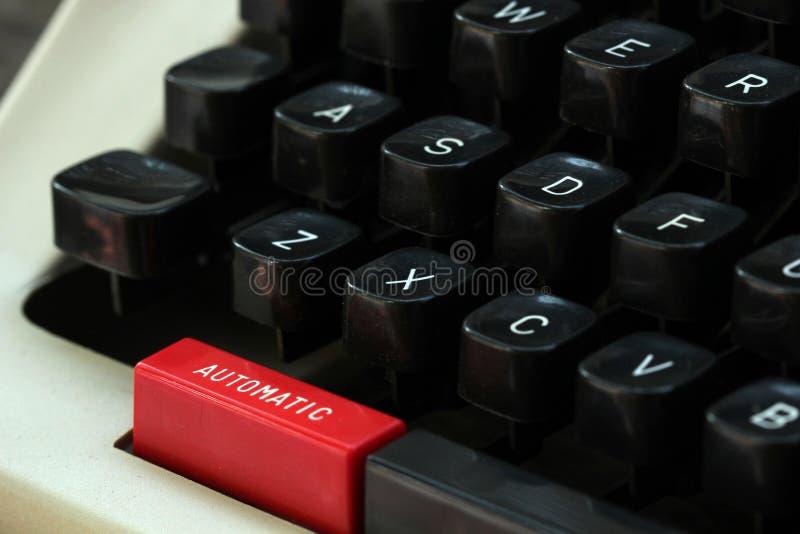 """Παλαιός συγγραφέας τύπων με το """"αυτόματο """"κουμπί στο κόκκινο χρώμα στοκ φωτογραφία"""