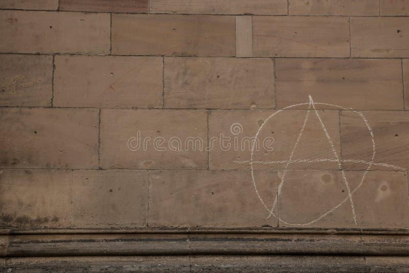Παλαιός τοίχος ενός ιστορικού κτηρίου με το γραπτό σημάδι αναρχίας στοκ εικόνες