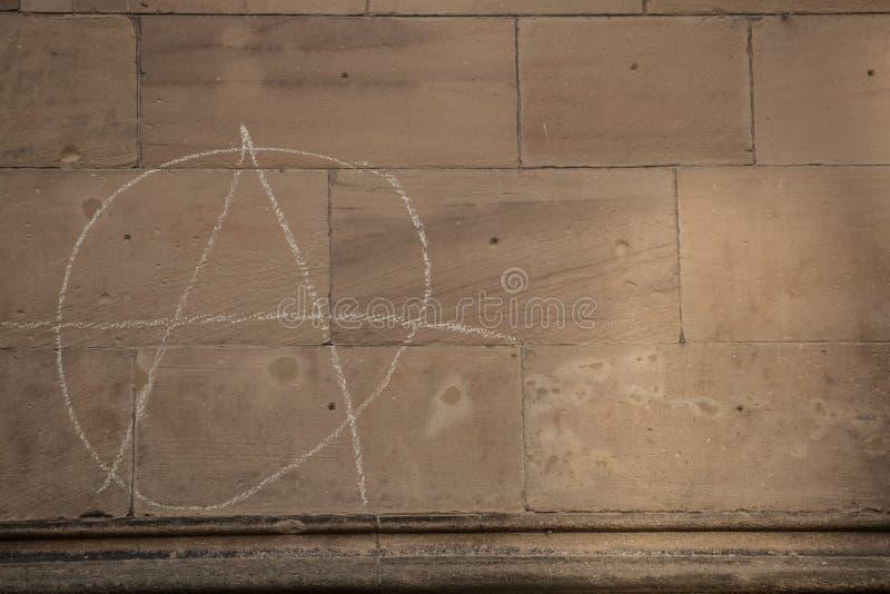 Παλαιός τοίχος ενός ιστορικού κτηρίου με το γραπτό σημάδι αναρχίας στοκ φωτογραφία με δικαίωμα ελεύθερης χρήσης