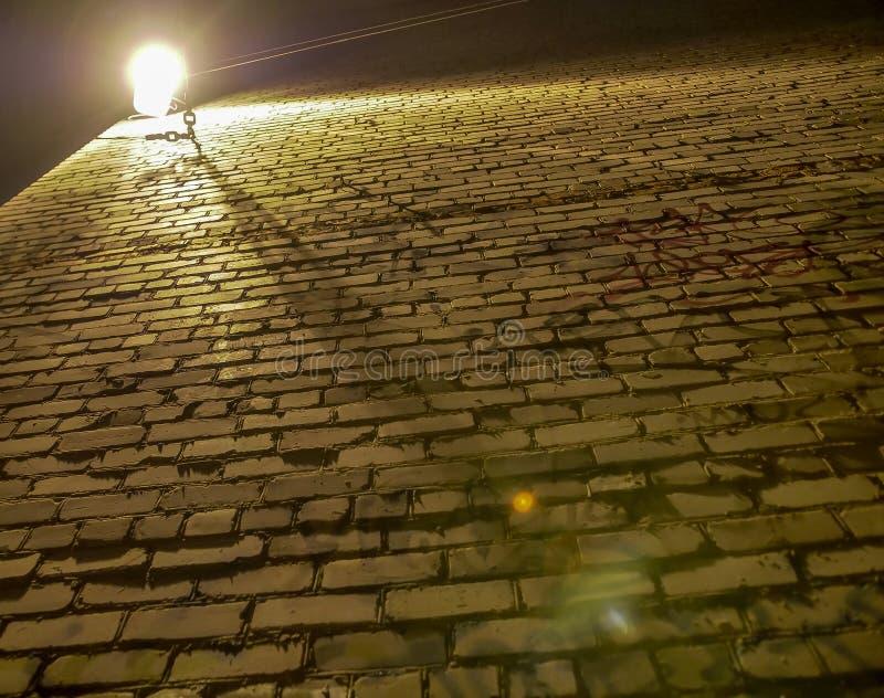 Παλαιός τραχύς και ανώμαλος τουβλότοιχος που φωτίζεται από ένα φανάρι, κατώτατη άποψη στοκ εικόνα με δικαίωμα ελεύθερης χρήσης