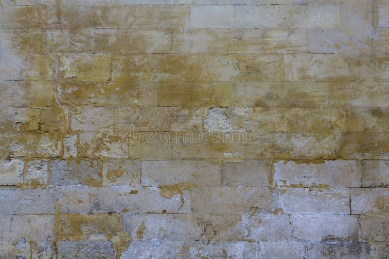 Παλαιός χαλασμένος γκρίζος τοίχος των μεγάλων τούβλων με τα κίτρινα σημεία του χρώματος r στοκ εικόνες με δικαίωμα ελεύθερης χρήσης