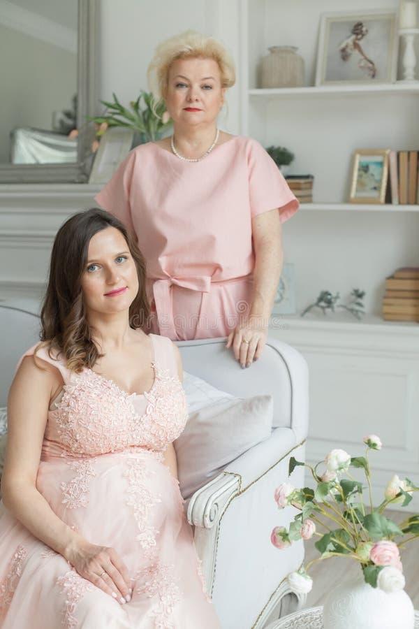 Παλαιότερη μητέρα και η ενήλικη έγκυος κόρη της στοκ εικόνες