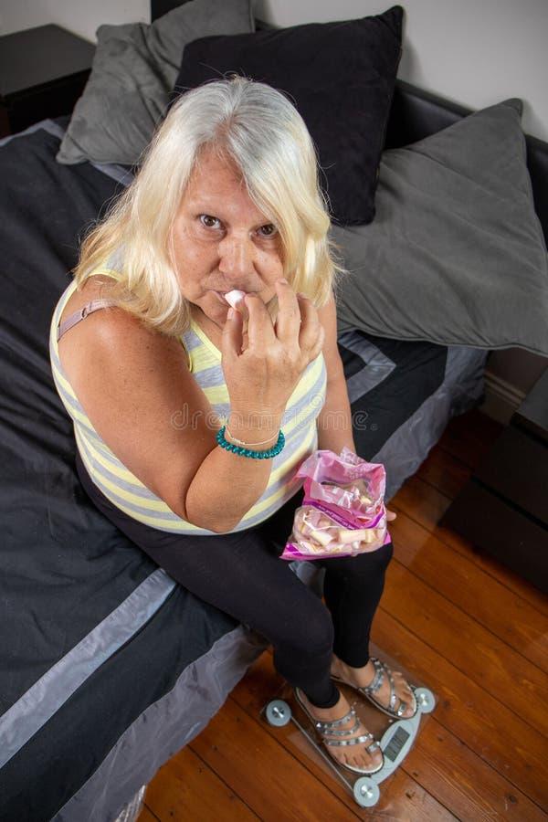 Παλαιότερη παχύσαρκη συνεδρίαση γυναικών κάτω στο κρεβάτι τρώγοντας την καραμέλα στοκ εικόνες με δικαίωμα ελεύθερης χρήσης