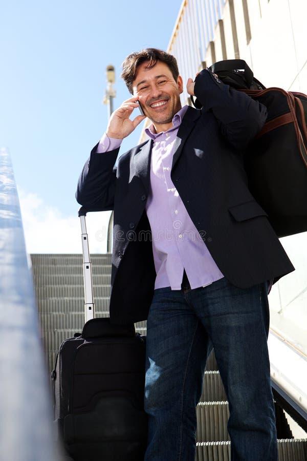 Παλαιότερος επιχειρηματίας που ταξιδεύουν με την τσάντα και τηλέφωνο που στέκεται στην κυλιόμενη σκάλα στοκ φωτογραφία με δικαίωμα ελεύθερης χρήσης