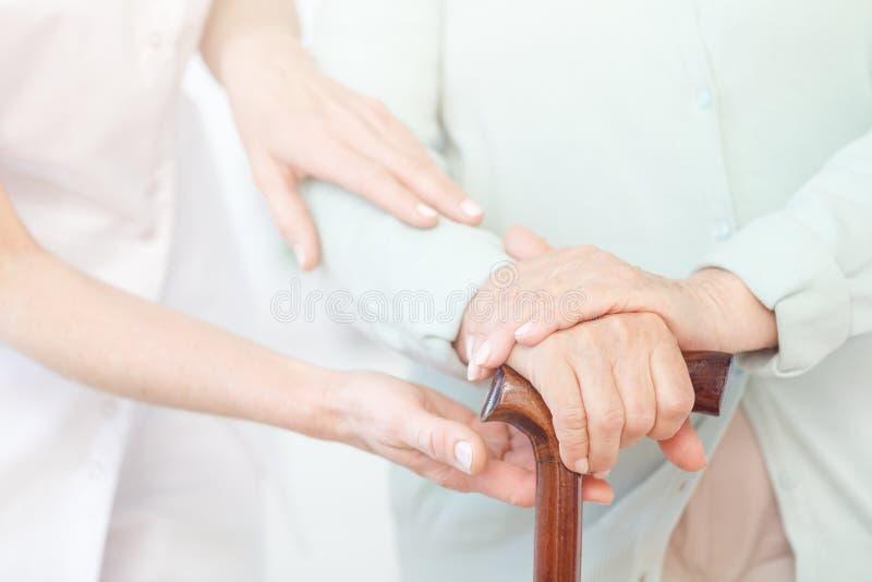 Παλαιότερος κρατά τα χέρια στο ραβδί περπατήματος στοκ εικόνα