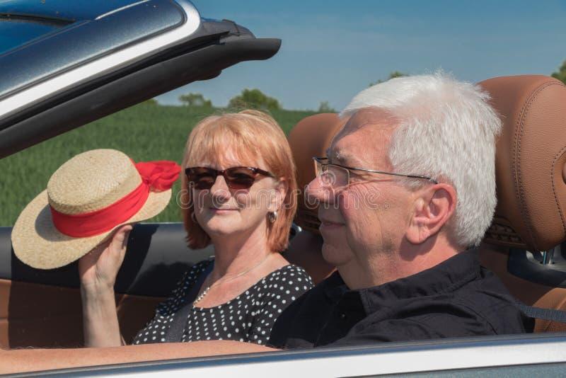 Παλαιότερο ζεύγος σε ένα μετατρέψιμο αυτοκίνητο πολυτέλειας μια ηλιόλουστη ημέρα στοκ φωτογραφίες με δικαίωμα ελεύθερης χρήσης