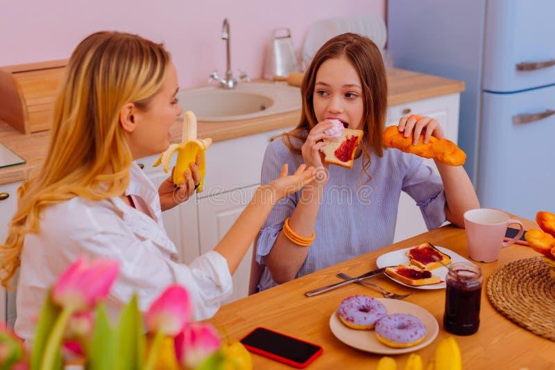 Παλαιότερο λέγοντας έφηβη αδελφών για τη ζημιά των γλυκών για την υγεία στοκ φωτογραφίες