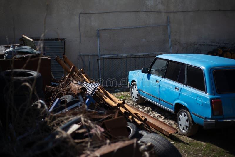 Παλαιό αναδρομικό μπλε αυτοκίνητο στην απόρριψη απορρίματος στοκ εικόνες