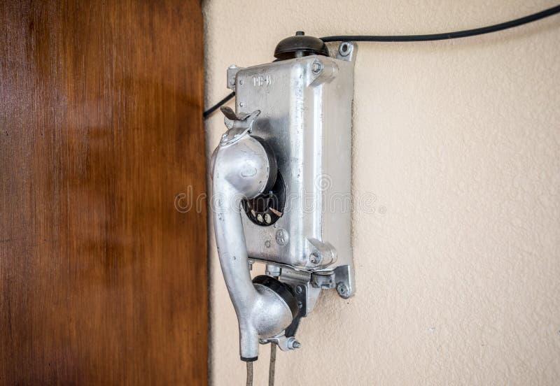 Παλαιό αναδρομικό τηλέφωνο σε έναν τοίχο γκρίζου στοκ φωτογραφία