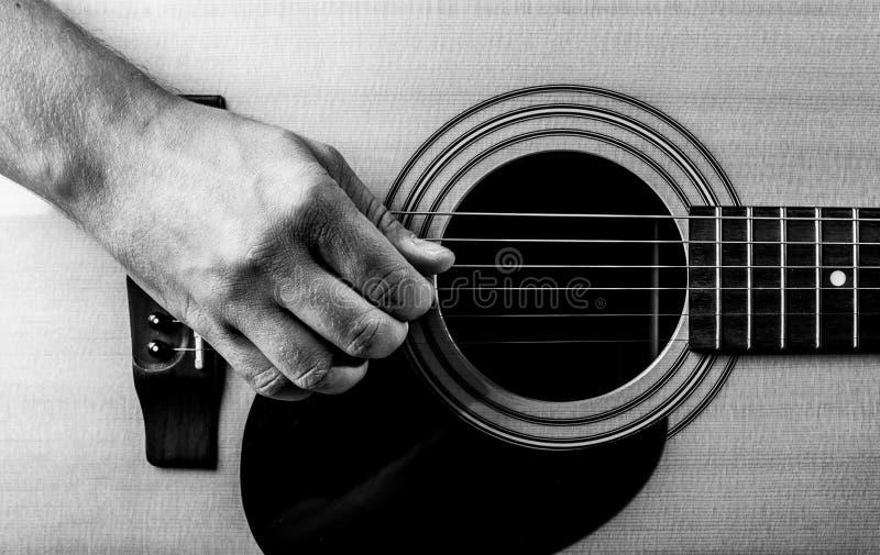 Παλαιό ανθρώπινο χέρι στις σειρές μιας ακουστικής κιθάρας Κινηματογράφηση σε πρώτο πλάνο στοκ φωτογραφία με δικαίωμα ελεύθερης χρήσης