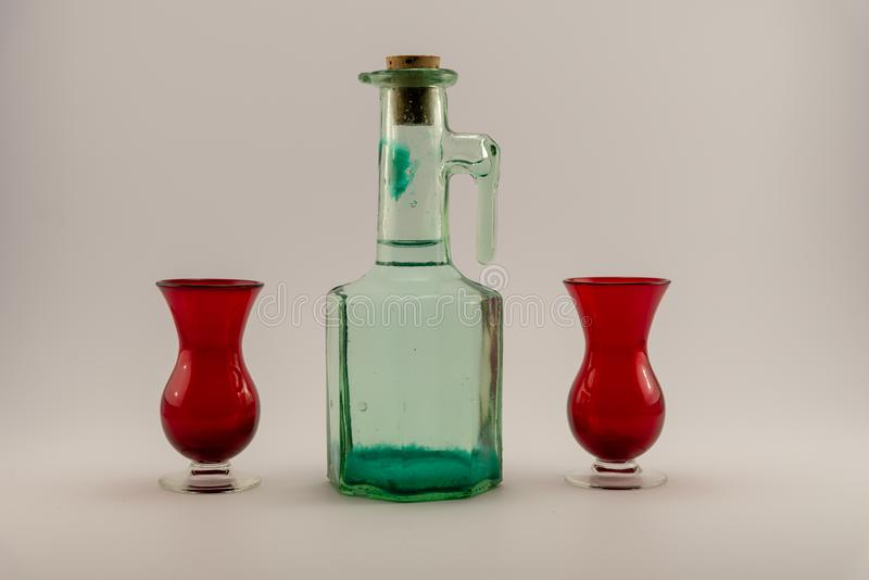 Παλαιό βουλωμένο μπουκάλι και κόκκινα πυροβοληθε'ντα γυαλιά στοκ φωτογραφία με δικαίωμα ελεύθερης χρήσης