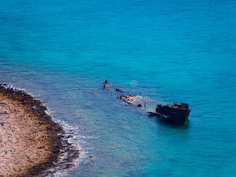 Παλαιό βυθισμένο σκάφος κοντά στη δύσκολη ακτή - όμορφο μπλε νερό στοκ φωτογραφίες με δικαίωμα ελεύθερης χρήσης