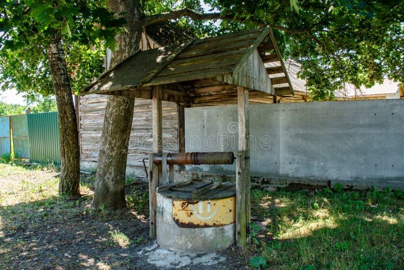 Παλαιό γλυκό νερό καλά κάτω από τη στέγη που βρίσκεται στο χωριό κατά τη διάρκεια της φωτεινής ηλιόλουστης ημέρας στοκ φωτογραφία με δικαίωμα ελεύθερης χρήσης