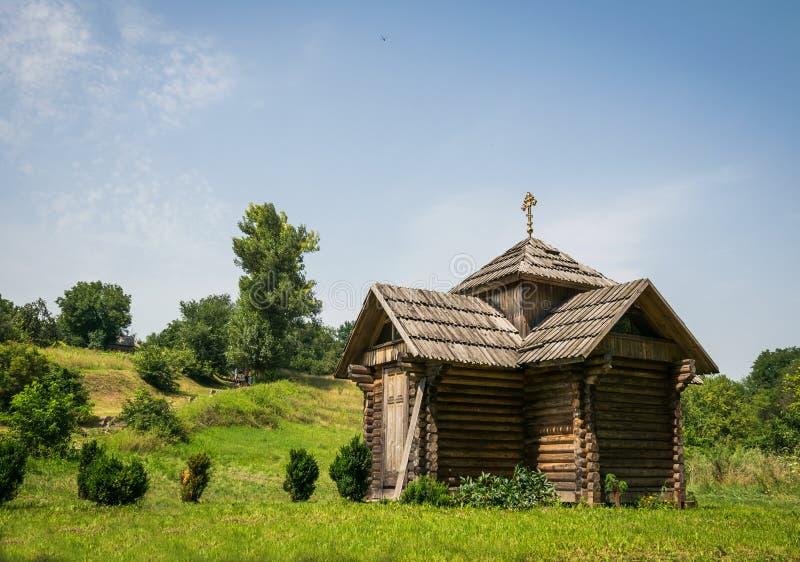 Παλαιό γραφικό ξύλινο του χωριού παρεκκλησι και ηλιόλουστο θερινό λιβάδι στοκ φωτογραφία με δικαίωμα ελεύθερης χρήσης