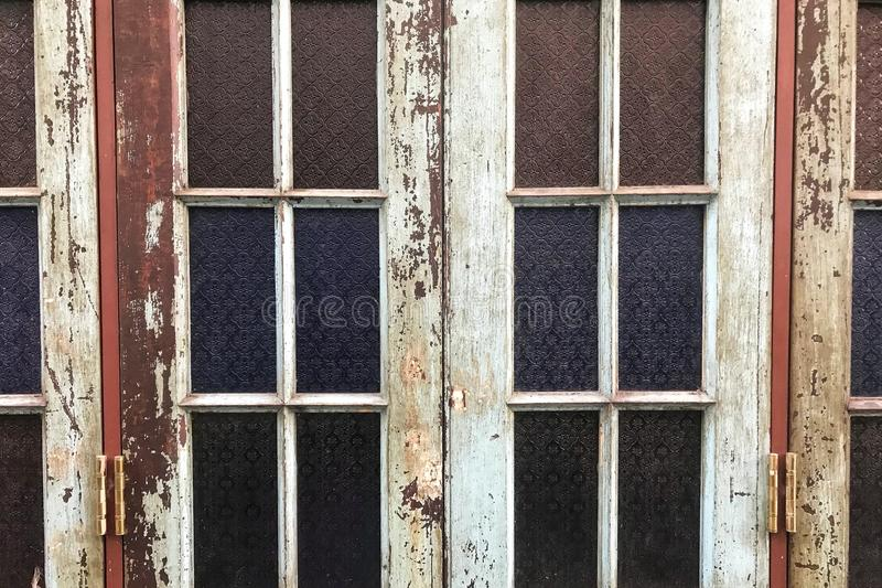 Παλαιό γυαλί λεκέδων με το κλασικό ύφος και ξεφλουδισμένος από τα χρώματα από το ξύλινο πλαίσιο στοκ εικόνες