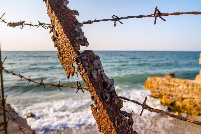 Παλαιό διαβρωμένο σκουριασμένο μέρος ενός εγκαταλειμμένου φάρου στην ακτή κοντά στις καταστροφές στοκ φωτογραφίες