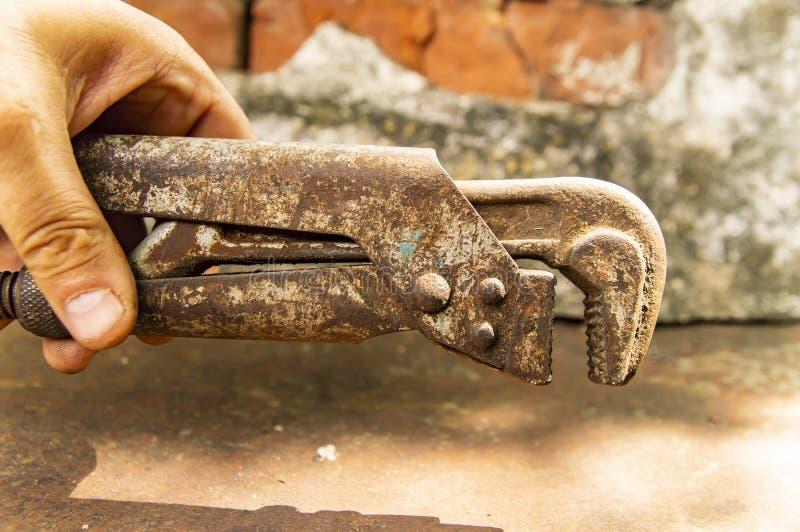 Παλαιό διευθετήσιμο γαλλικό κλειδί στο χέρι υδραυλικών - ένα εργαλείο εργασίας στοκ φωτογραφίες με δικαίωμα ελεύθερης χρήσης