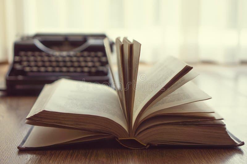 Παλαιό εκλεκτής ποιότητας βιβλίο με το backlight και και παλαιά γραφομηχανή στο υπόβαθρο στοκ φωτογραφία με δικαίωμα ελεύθερης χρήσης