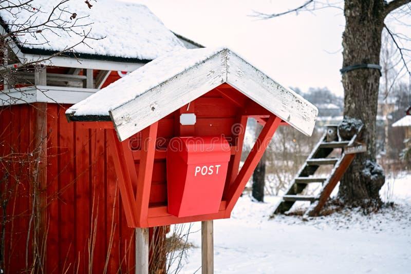 Παλαιό εκλεκτής ποιότητας κόκκινο ξύλινο μετα κιβώτιο ταχυδρομείου στο χωριό επαρχίας το χειμώνα στοκ εικόνες