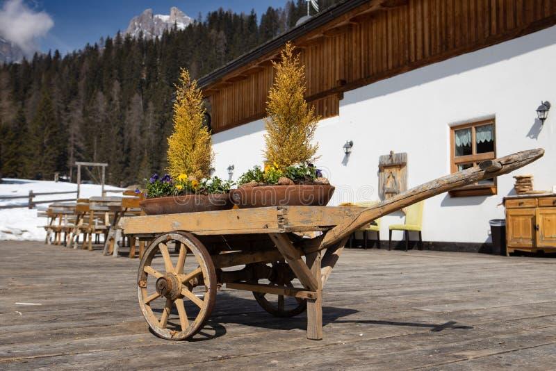 """Παλαιό εκλεκτής ποιότητας wheelbarrow με τα λουλούδια σε το κοντά σε Cortina δ """"Ampezzo, δολομίτες, Ιταλία στοκ εικόνες"""