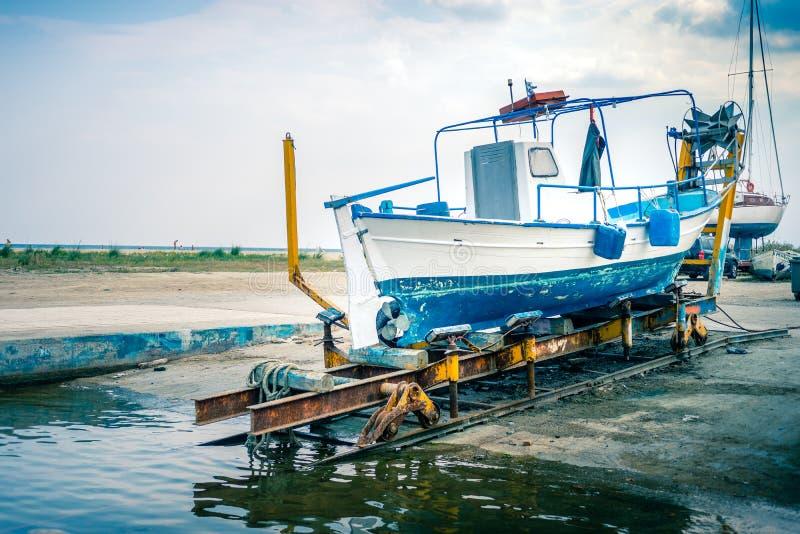 Παλαιό ελληνικό αλιευτικό σκάφος στα μπλε άσπρα χρώματα ξηρών αποβαθρών, Κα Paralia στοκ εικόνα με δικαίωμα ελεύθερης χρήσης