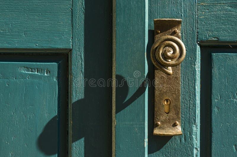 Παλαιό εξόγκωμα πορτών ορείχαλκου με την περιτυλιγμένη λαβή στην πράσινη ξύλινη πόρτα στοκ φωτογραφία με δικαίωμα ελεύθερης χρήσης