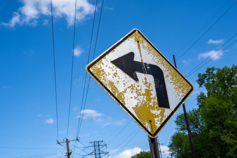 Παλαιό, κίτρινο οδικό σημάδι καμπυλών μπροστά με το χρώμα αποφλοίωσης ενάντια στο μπλε ουρανό με τα ηλεκτροφόρα καλώδια στοκ εικόνες