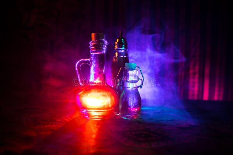 Παλαιό και εκλεκτής ποιότητας μπουκάλι γυαλιού στο σκοτεινό ομιχλώδες υπόβαθρο με το φως Δηλητήριο ή μαγική υγρή έννοια στοκ εικόνες με δικαίωμα ελεύθερης χρήσης