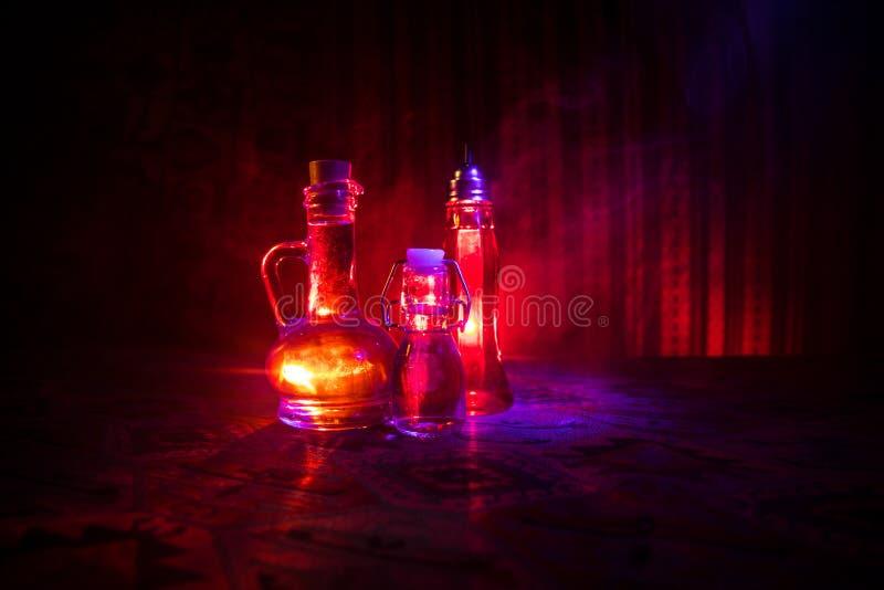 Παλαιό και εκλεκτής ποιότητας μπουκάλι γυαλιού στο σκοτεινό ομιχλώδες υπόβαθρο με το φως Δηλητήριο ή μαγική υγρή έννοια στοκ εικόνες