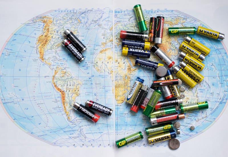 Παλαιό κενό Batteris στο ένα χρησιμοποιούμενο μόνο ανατρεμμένος στον παγκόσμιο χάρτη στοκ φωτογραφίες