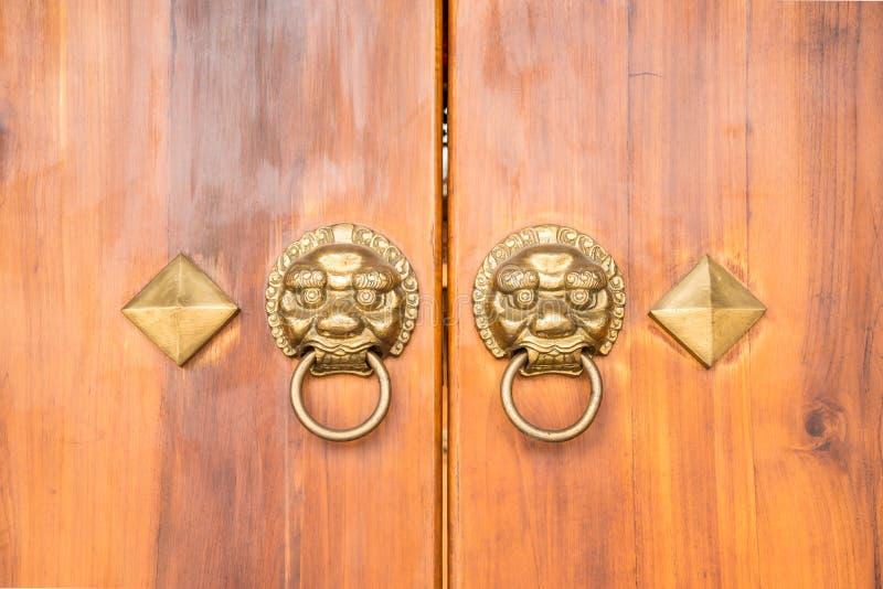 Παλαιό κινεζικό ξύλινο ύφος πορτών με τα επικεφαλής ρόπτρα λιονταριών στοκ φωτογραφία