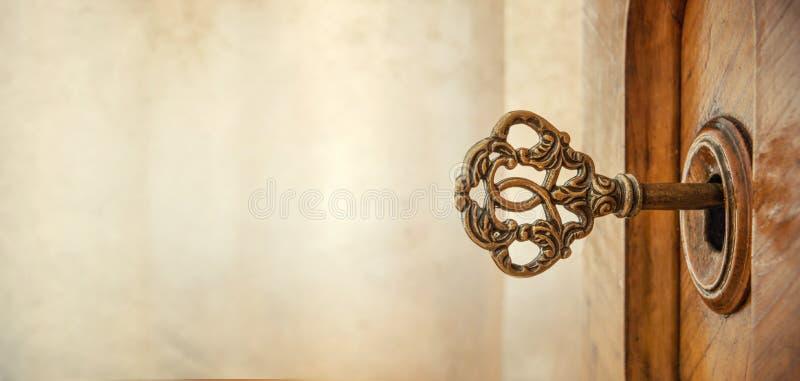 Παλαιό κλειδί στην κλειδαρότρυπα, μακρο πυροβολισμός αναδρομικό ύφος Έννοια και ιδέα FO στοκ φωτογραφία