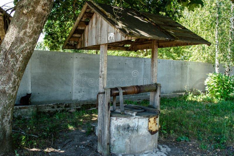 Παλαιό κρύο νερό καλά κάτω από τη στέγη που βρίσκεται στο χωριό κατά τη διάρκεια της φωτεινής ηλιόλουστης ημέρας στοκ φωτογραφίες με δικαίωμα ελεύθερης χρήσης