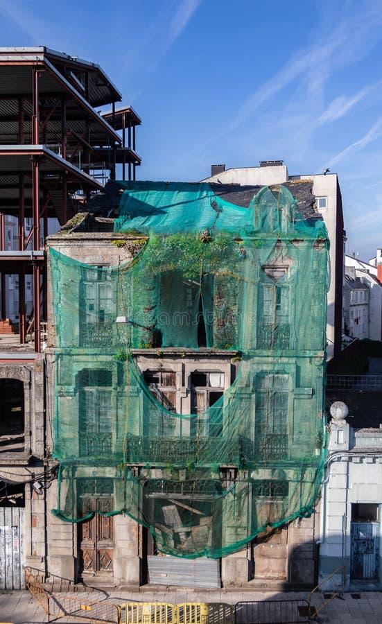 Παλαιό κτήριο πετρών ακατοίκητο και στις καταστροφές, που καλύπτονται από ένα πράσινο ύφασμα Της Γαλικίας πόλη Lugo, Ισπανία στοκ εικόνες