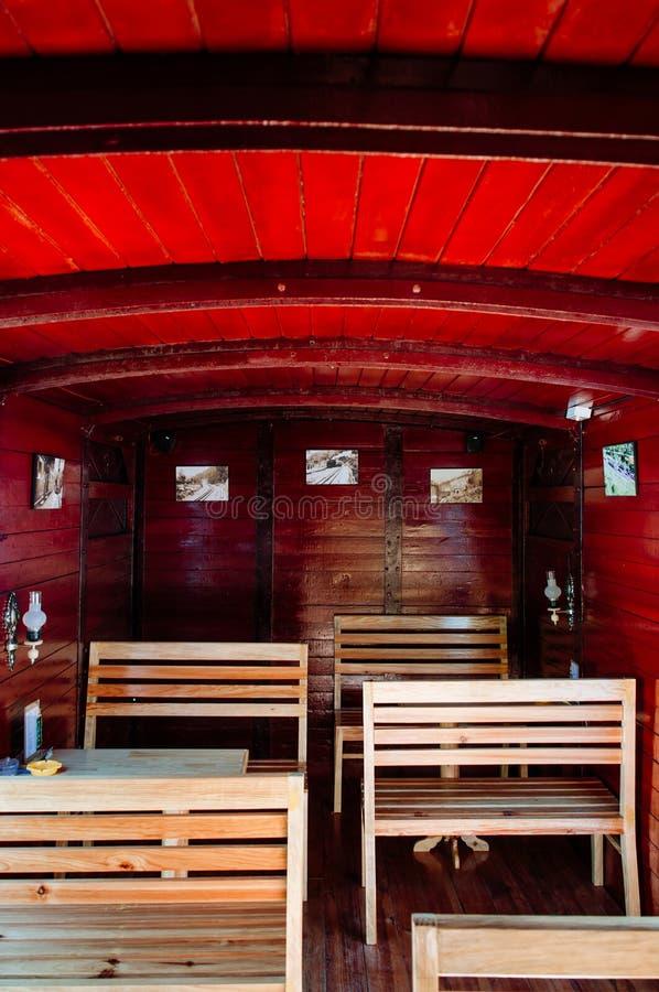 Παλαιό κόκκινο ξύλινο εσωτερικό αυτοκινήτων τραίνων με τα καθίσματα κ στοκ φωτογραφία με δικαίωμα ελεύθερης χρήσης