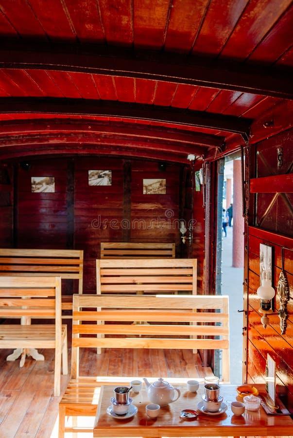 Παλαιό κόκκινο ξύλινο εσωτερικό αυτοκινήτων τραίνων με τα καθίσματα και τον πίνακα στοκ φωτογραφίες