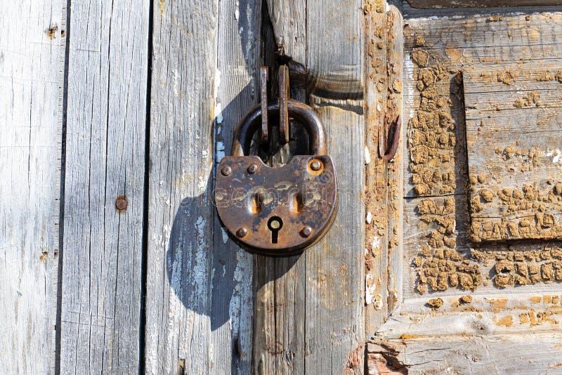 Παλαιό λουκέτο σε μια ξύλινη πόρτα Βαριά κλειδαριά σιδήρου σιτοβολώνων στοκ φωτογραφίες