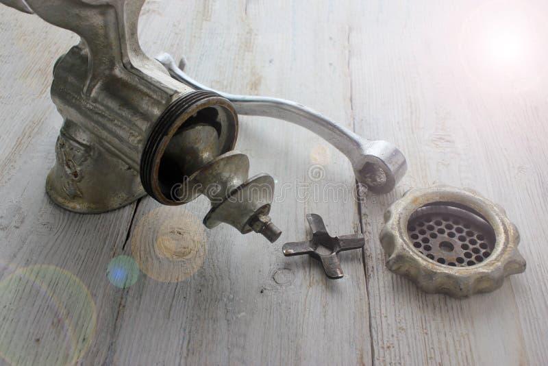 Παλαιό μηχανή κοπής κιμά σε έναν ξύλινο πίνακα, μικρολεπτομέρειες, ανταλλακτικά Στρίψτε το κρέας σε ένα μηχανή κοπής κιμά λειτουρ στοκ εικόνα με δικαίωμα ελεύθερης χρήσης