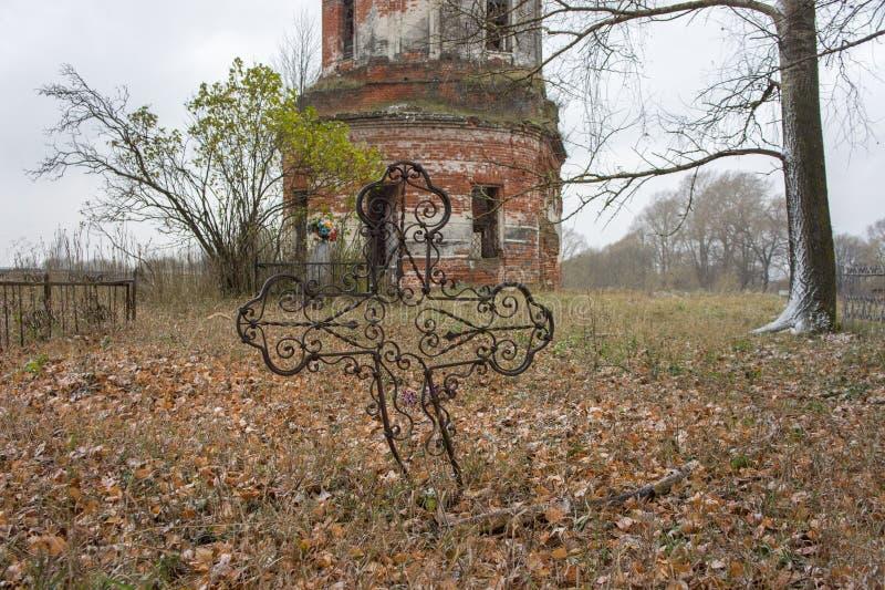 Παλαιό νεκροταφείο κοντά σε μια εγκαταλειμμένη εκκλησία στοκ φωτογραφία