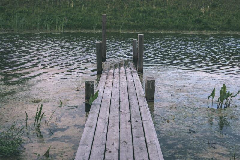 παλαιό ξύλινο ίχνος θαλασσίων περίπατων σανίδων στο κοντινό νερό περιοχής ελών - vint στοκ φωτογραφίες