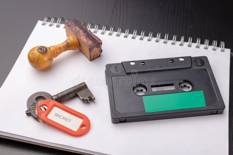 Παλαιό ξύλινο γραμματόσημο και μια ταινία κασετών σε ένα άσπρο κομμάτι του σημειωματάριου Ένα κλειδί για τις μυστικές καταγραφές  στοκ φωτογραφία με δικαίωμα ελεύθερης χρήσης