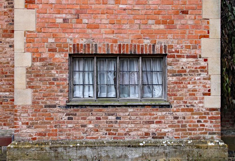 Παλαιό ξύλινο παράθυρο σε έναν ξεπερασμένο τουβλότοιχο σε ένα παλαιό σπίτι φέουδων στοκ φωτογραφία με δικαίωμα ελεύθερης χρήσης