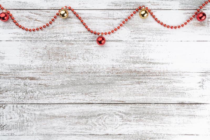 Παλαιό ξύλινο υπόβαθρο Χριστουγέννων Γιρλάντες και κόκκινα μπιχλιμπίδια Ευχετήρια κάρτα Χριστουγέννων Τοπ όψη διαστημικό κείμενό  στοκ εικόνες