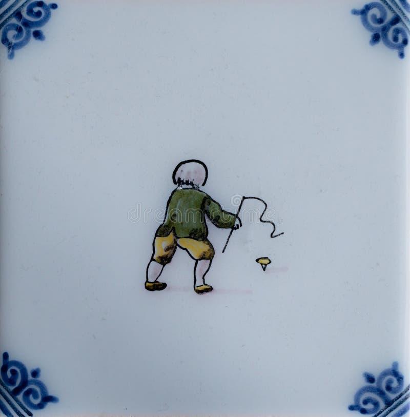 Παλαιό ολλανδικό κεραμίδι που παρουσιάζει ένα παιδί με μια γόμφος-κορυφή στοκ εικόνες